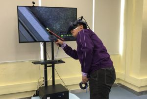 A trainee demonstrates how he uses VR technology to learn how to repair lifts..