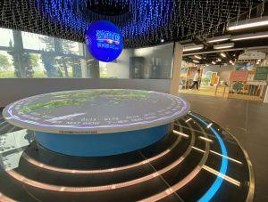 图示展城馆的新展品—「规划视窗」,透过一个像眼球的圆形屏幕,配合香港地貌模型上的互动投影,加上声光效果,带访客进入一段探索香港规划与基建发展的旅程。.
